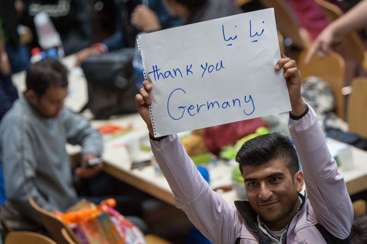 "A refugge holds up a sign on which he wrote ""Thank you Germany"""