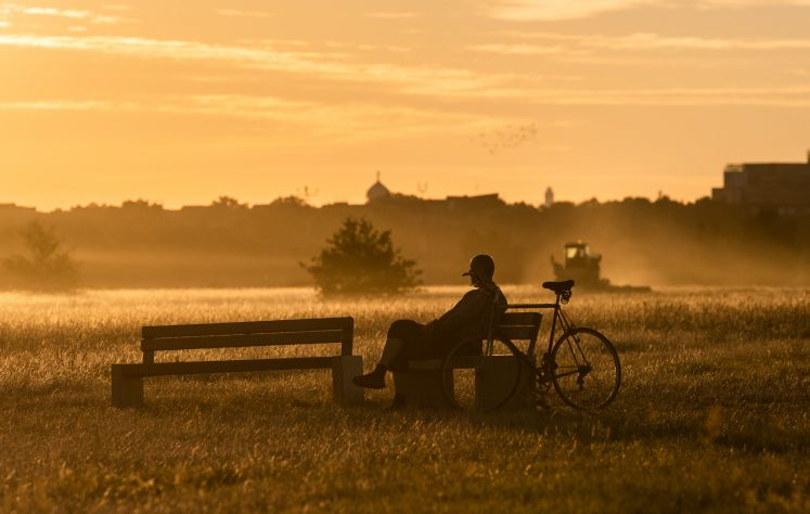 13 August 2018, Germany, Berlin: A man enjoys the morning atmosphere in the light of the rising sun on the Tempelhofer Feld.